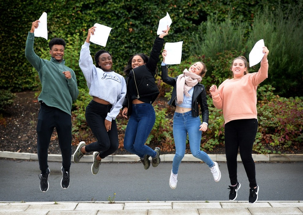 students jumping with exam results celebrating